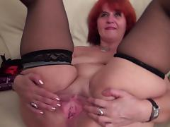 Mature redhead hussy in stockings pleasures her wet pussy